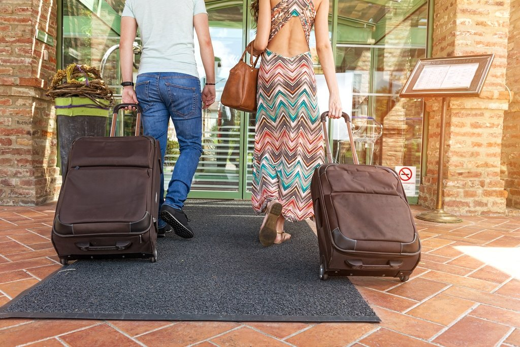 Young couple standing at hotel corridor upon arrival, looking for room, holding suitcases; Shutterstock ID 205281238; Departmental Cost Code : 162800; Project Code: GBLMKT; PO Number: GBLMKT; Other: