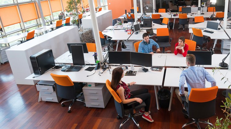 four tech workers in an open office space